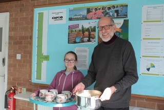 Hannah (Confirmati) and Jeff serving soup. The background shows a thermometer to display how much money St Dunstan's Parish have collected for CAFOD this Lent.