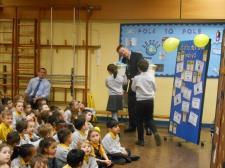 Head teacher encourages students to continue carrying the bucket